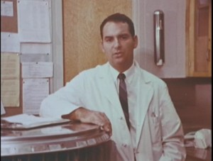 A dark-haired man wearing a white medical coat leans against a counter in a hospital.