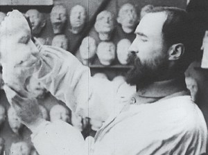 A man in a smock holds up a plaster cast of a face.
