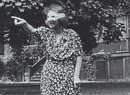 A masked woman wearing a patterned dress stands outside and makes pointing gestures to someone or thing off screen.