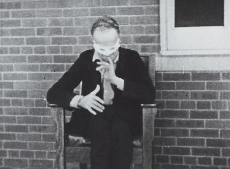 A male patient wearing a white mask sits in front of a brick wall and gestures with his fingers extended.
