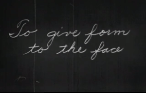 Cursive writing on blackboard: 'To give form to the face.