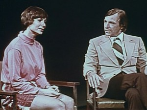 A man and woman sit in chairs as on a talk show.