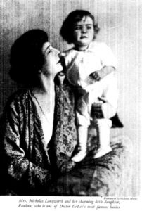 A woman looks up at a small child she holds on her shoulder.