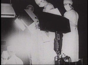 Film still of people in surgical clothes filming an operation under bright lights.