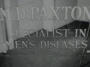 """A Doctor's office window sign reads """"M.D. Paxton Specialist in Men's Diseases."""