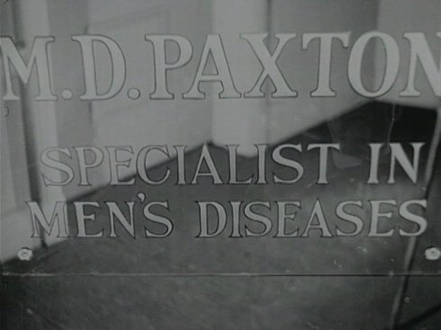 "A Doctor's office window sign reads ""M.D. Paxton Specialist in Men's Diseases."