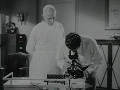 Men in scrubs use a microscope.