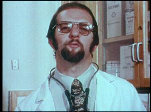 A man in a white coat and stethescope talks to the camera.