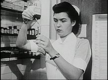 A woman in a white nurses uniform measures out medication.