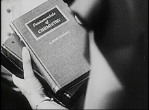 A woman holds a stack of books, the top one reads Fundamentals of Chemistry.