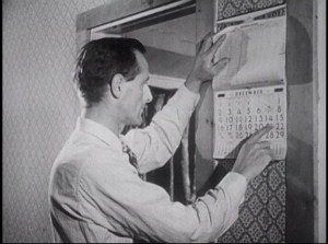 A man in a shirt and tie checks a wall calendar.