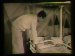 A sailor leans over to talk to a patient in a shipboard hospital cot.