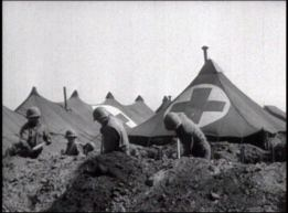 Men in military uniforms and helmets dig with shovels around a medical encampment.