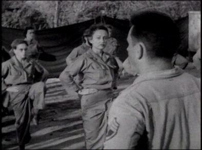 Women in military uniforms exercize outdoors at a sargent's direction.