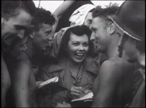 A smiling young woman writes in a notebook surrounded by young men.