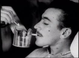 A man is helped to smoke something from a modified can.