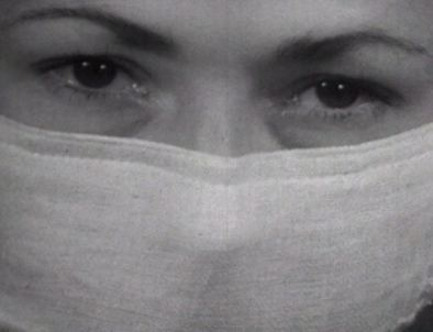 A close up of a woman's face in a surgical mask.