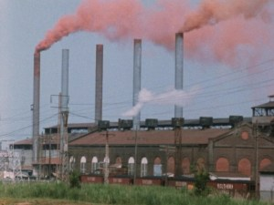 Brown smoke coming out of tall pipes from a factory behind smaller buildings