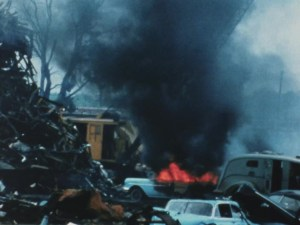 car surrounding a small pit of fire and black smoke coming out of some canisters