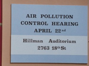 Blue sign that says : Air Pollution Control Hearing Aprill 22nd, Hillman Auditorium 2763 18th St