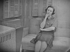 Woman in a collared shirt and pencil skirt sitting on a couch with her fist on her chin.
