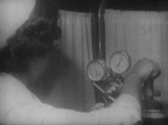 A woman adjusts a gass cylinder gague.