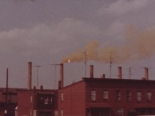 Smokestacks over brick buildings.