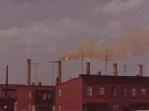 Smokestacks over brick buildings.