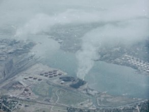 An aerial view of a smoking powerplant on a river.