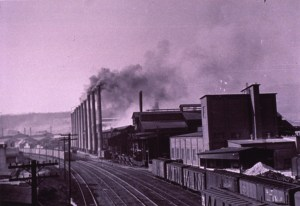 A row of smokestacks along a railroad track in an industrial area.