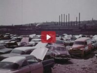 Cars in a junkyard sit next to factory smokestacks.