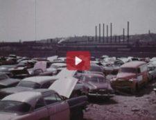 Cars in a junkyard sit next to factory smokestacks.