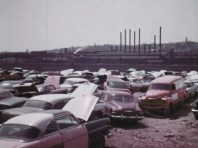 a bunch of old broken cars in front a big ship