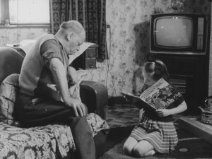 a child reading a book on the floor to a old man on the couch.