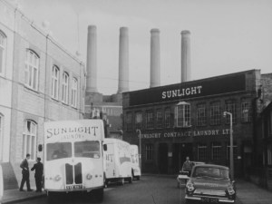 a building that says sunlight contract laundry LTD and behind is a factory with four large tube chimneys coming out of it