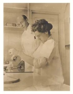 a man and a women in white lab coats doing testing