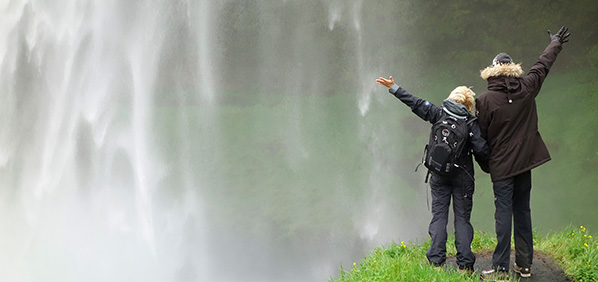 photo of 2 people in parkas standing on a small bluff overlooking a massive waterfall