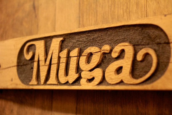 "The word ""MUGA"" carved in wood"