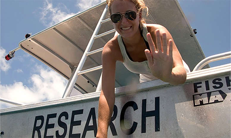 "a woman leaning off the back of a boat. On the boat's stern are large letters spelling ""research"""