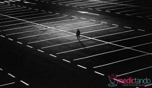 Homem caminhando em estacionamento de supermercado. Foto em preto e branco.