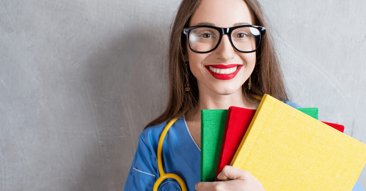 Portrait of a young nurse with colorful books and stethoscope on a wray wall background