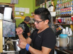 Jorge Jimenez, the cafe's morning manager, steams milk for a customer. Every staff member Delgado hires speaks Spanish—many customers do not speak English.