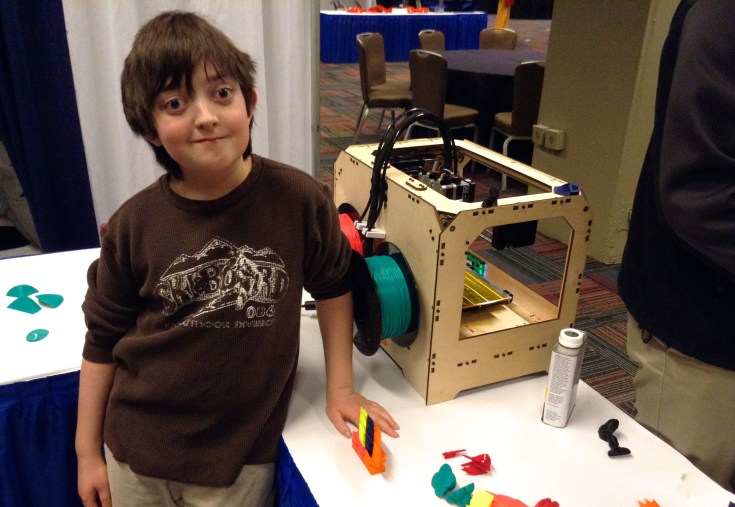 """Benjamin Kocian, 10, of Naperville, stands proud next to his puzzle creation. """"Geometry is far better than normal math,"""" he says."""