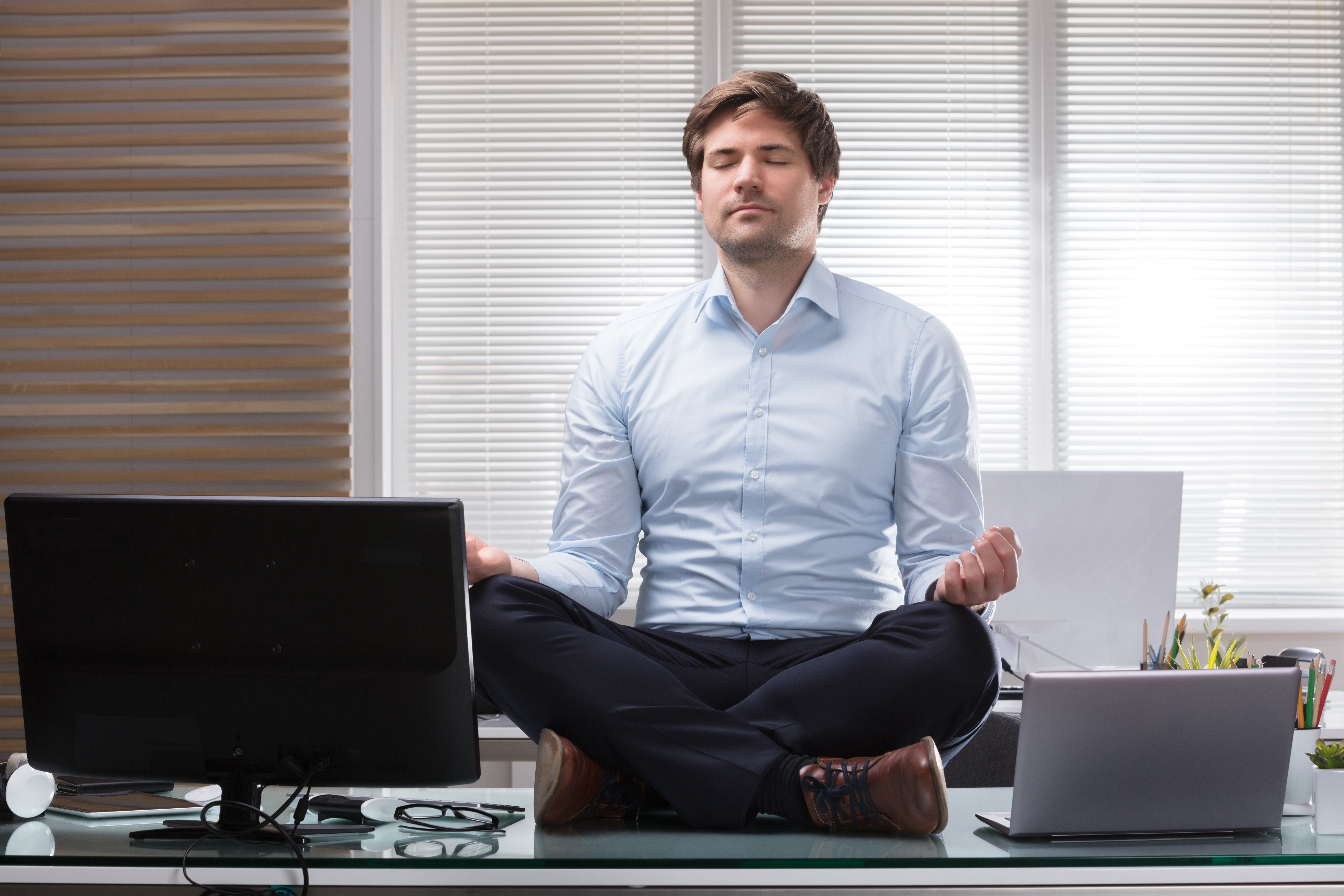 Young Businessman Sitting On Desk Meditating In Office