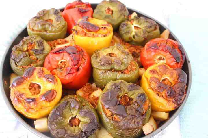 Albanian Stuffed Peppers - Picture shows a round baking tray with lots of stuffed bell peppers