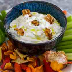 A bowl of sour cream dip in the middle of chips and vegetables. Dip is garnished with walnuts and olive oil.