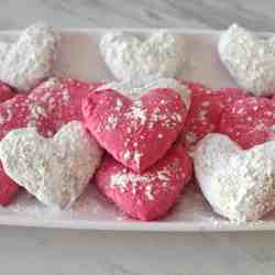 Valentine's Mediterranean Almond Cookies, white and pink heart shaped cookies covered in confectioner's sugar