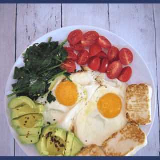 Low carb breakfast made with eggs, fried halloumi slices, spinach, avocado and tomatoes