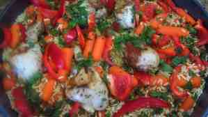 Prepping baking tray with chicken, orzo and veggies