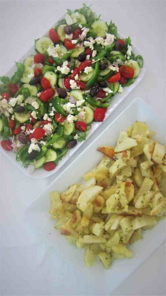 Arugula salad with tomatoes, cucumbers, green peppers, feta cheese, olives and olive oil as well as roasted potatoes.